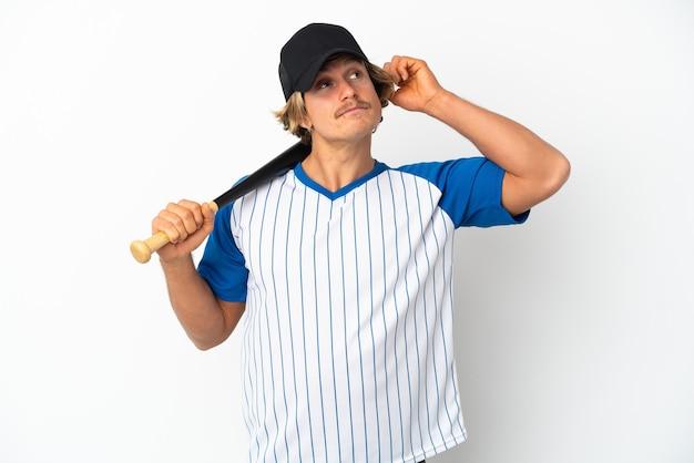 Młody blondyn na białym tle na białej ścianie, grając w baseball i mając wątpliwości z mylącym wyrazem twarzy