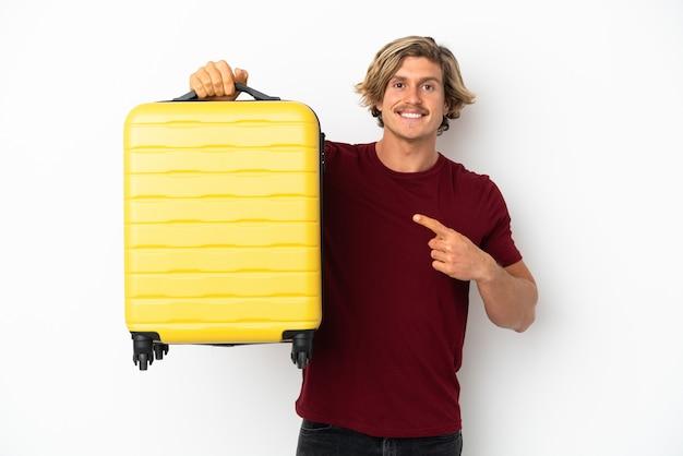 Młody blondyn na białym tle na białym tle w wakacje z walizką podróżną