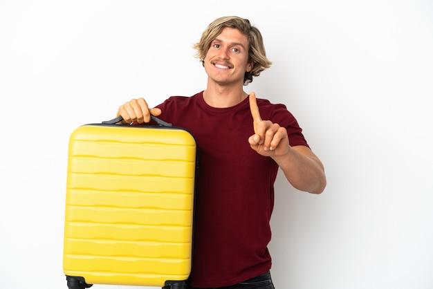 Młody blondyn na białym tle na białym tle w wakacje z walizką podróży i licząc jeden