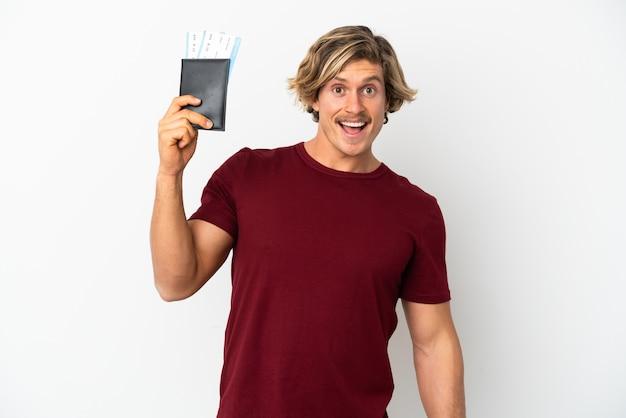 Młody blondyn na białym tle szczęśliwy na wakacjach z biletami paszportowymi i lotniczymi