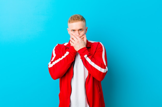 Młody blondyn noszący sportowe ubrania zakrywające usta dłońmi z zszokowanym, zaskoczonym wyrazem twarzy, utrzymujący tajemnicę lub mówiąc: ups