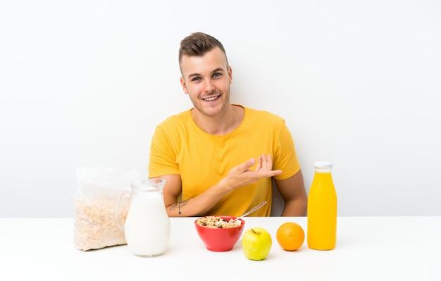 Młody blondyn o śniadanie, rozkładając ręce na bok za zaproszenie