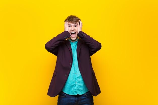 Młody blondyn podnosząc ręce do głowy, z otwartymi ustami, czując się wyjątkowo szczęśliwy, zaskoczony, podekscytowany i szczęśliwy izolowany ponad ścianą
