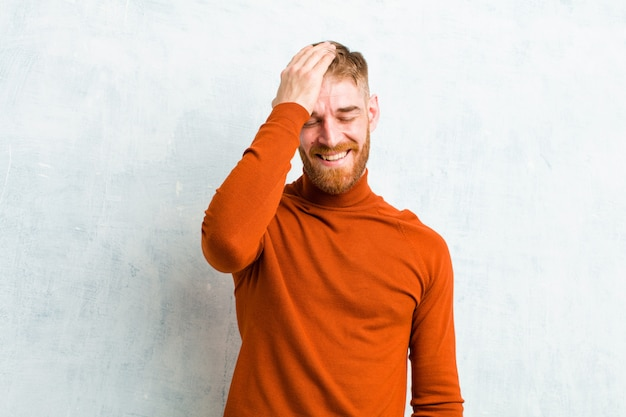 Młody blondyn śmieje się i bije w czoło