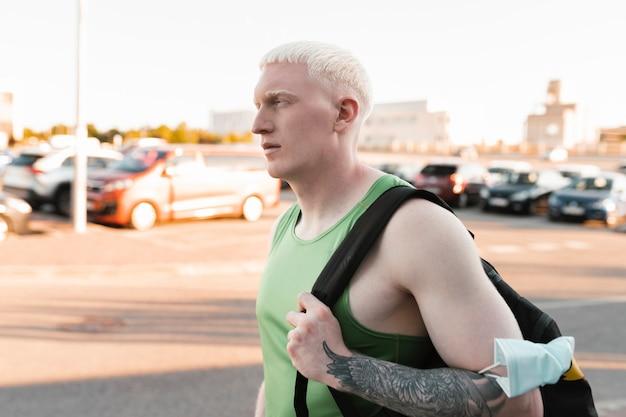 Młody blondyn sportowy i plecak, idzie ulicą goes