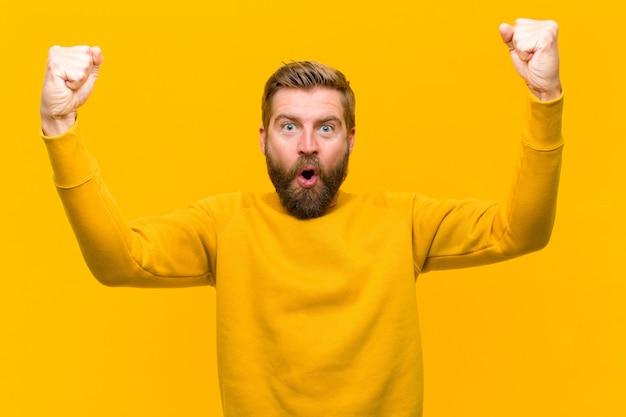 Młody blondyn świętuje niewiarygodny sukces jak zwycięzca, wyglądając na podekscytowanego i radosnego mówiąc: weź to! o pomarańczową ścianę