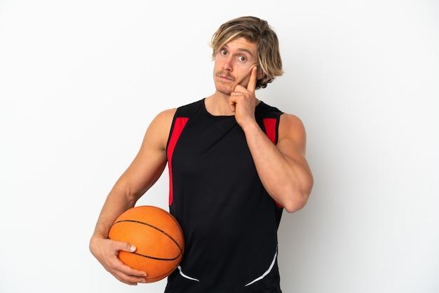 Młody blondyn trzymający piłkę do koszykówki na białym tle myślący pomysł