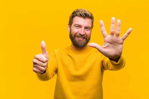 Młody blondyn uśmiecha się i wygląda przyjaźnie, pokazując numer sześć lub szósty ręką do przodu, odliczając