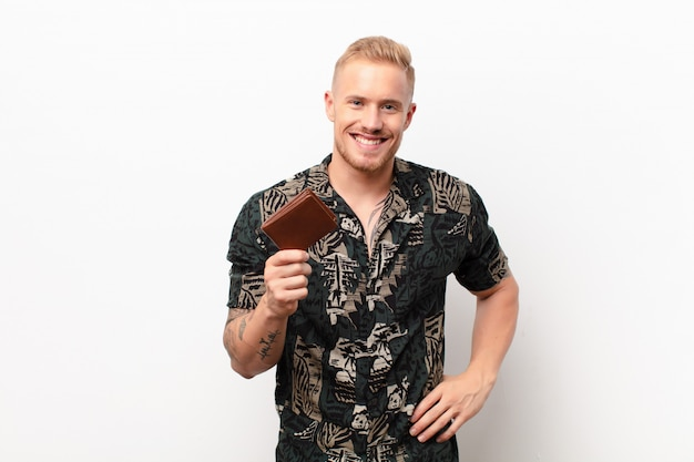 Młody blondyn uśmiecha się radośnie z ręką na biodrze i pewną siebie, pozytywną, dumną i przyjazną postawą z portfelem