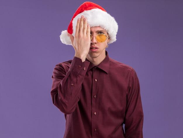 Młody blondyn w kapeluszu santa i okularach patrząc na kamery obejmujące połowę twarzy ręką na białym tle na fioletowym tle z miejsca na kopię