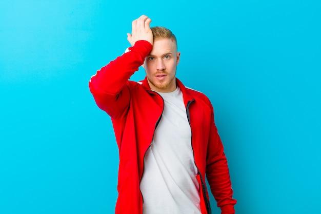 Młody blondyn w sportowym stroju podnoszącym dłoń do czoła, pomyślał, po popełnieniu głupiego błędu lub zapamiętania, czując się głupio