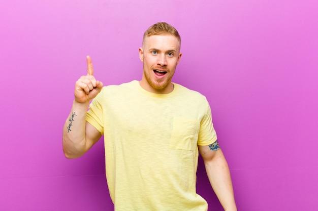 Młody blondyn w żółtej koszulce czuje się jak szczęśliwy i podekscytowany geniusz po realizacji pomysłu, radośnie podnosząc palec, eureka!