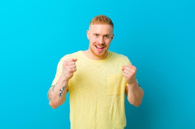 Młody blondyn w żółtej koszulce czuje się zszokowany, podekscytowany i szczęśliwy, śmiejąc się i świętując sukces, mówiąc: wow!