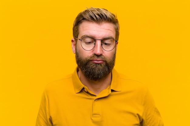 Młody blondyn, wyglądający głupio i zabawnie, z głupim wyrazem twarzy, żartuje i wygłupia się na pomarańczowej ścianie