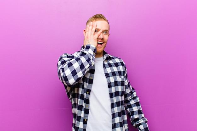 Młody blondyn z kwadratową koszulą, wyglądający na zszokowanego, przestraszonego lub przerażonego, zakrywający twarz dłonią i zaglądający między palce