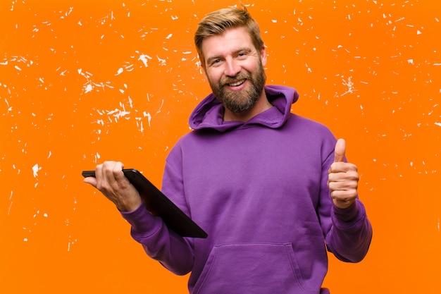 Młody blondyn z tabletem w purpurowej bluzie z kapturem uszkodził pomarańczową ścianę