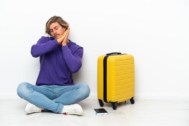 Młody blondyn z walizką, siedząc na podłodze, robiąc gest spania
