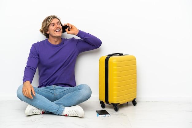 Młody blondyn z walizką siedzi na podłodze, prowadząc rozmowę z telefonem komórkowym