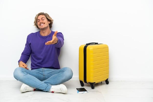 Młody blondyn z walizką siedzi na podłodze, ściskając ręce za dobre zamknięcie