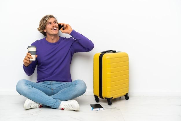 Młody blondyn z walizką siedzi na podłodze, trzymając kawę na wynos i telefon komórkowy