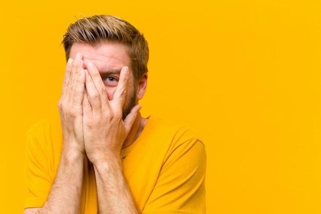 Młody blondyn zakrywa twarz rękami, zerkając między palcami ze zdziwionym wyrazem twarzy i patrząc w bok na pomarańczową ścianę