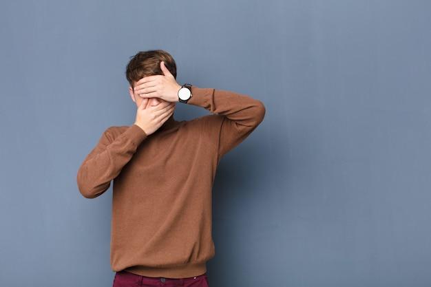 """Młody blondyn zakrywający twarz obiema rękami mówi """"nie""""! odmawianie zdjęć lub zakaz zdjęć umieszczonych na płaskiej ścianie"""