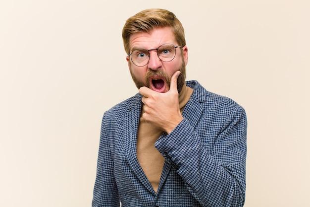 Młody blondynka biznesmen z szeroko otwartymi ustami i oczami i dłonią na brodzie, nieprzyjemnie zszokowany, mówiąc co lub wow