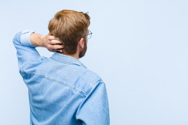 Młody blondynka dorosły mężczyzna myśli lub wątpliwości, drapanie głowy, czuje się zdziwiony i zdezorientowany, widok z tyłu lub z tyłu