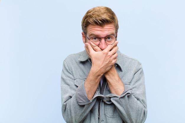 Młody blondynka dorosły mężczyzna obejmujące usta dłońmi z zszokowanym, zaskoczonym wyrazem twarzy, trzymając w tajemnicy lub mówiąc, ups