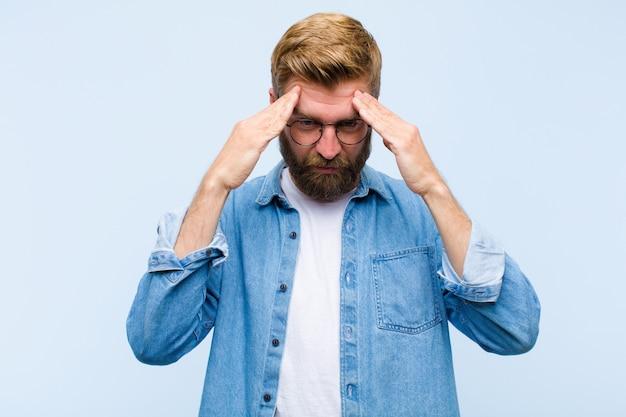 Młody blondynka dorosły mężczyzna szuka zestresowanej i sfrustrowanej pracy pod presją z bólem głowy i kłopotów z problemami