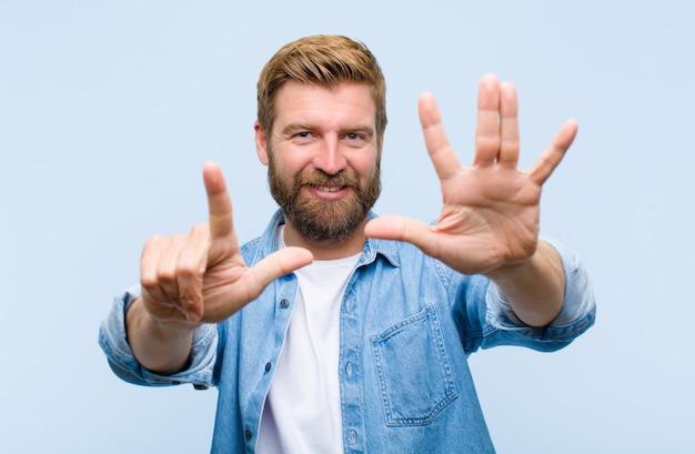 Młody blondynka dorosły mężczyzna uśmiecha się i szuka przyjazny, pokazując numer siedem lub siódmy z ręką do przodu, odliczając