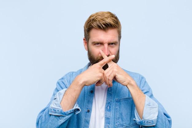 Młody blondynka dorosły mężczyzna wyglądający poważnie i niezadowolony z obu palców skrzyżowanych w przód z odrzuceniem, prosząc o ciszę