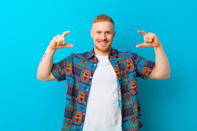 Młody blondynka mężczyzna jest ubranym druk koszula obramia lub zarysowywa własnego uśmiech obiema rękami, patrzeje pozytywny i szczęśliwy, wellness pojęcie