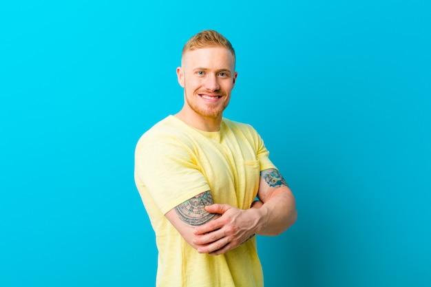 Młody blondynka mężczyzna jest ubranym żółtą t koszula ono uśmiecha się kamera z krzyżować rękami i szczęśliwy, ufny, zadowolony wyrażenie, boczny widok
