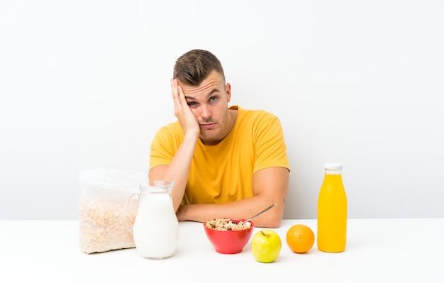 Młody blondynka mężczyzna ma śniadanie nieszczęśliwego i sfrustrowanego