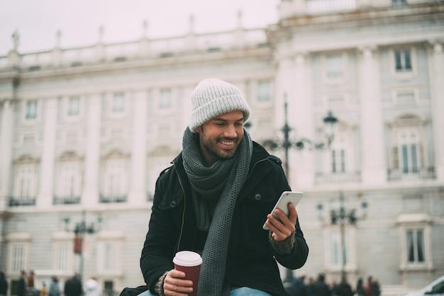 Młody blondynka mężczyzna na telefonie komórkowym i pić kawę blisko pałac królewskiego w zimie
