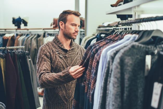 Młody blondynka mężczyzna robi zakupy w sklepie