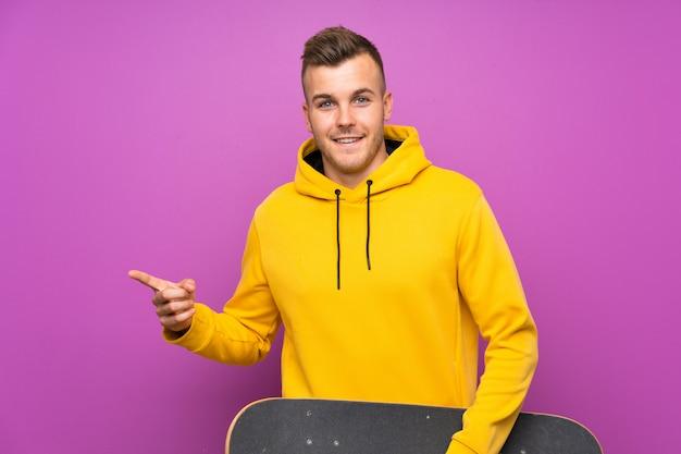 Młody blondynka mężczyzna trzyma łyżwę zaskakującą i wskazuje palec z boku