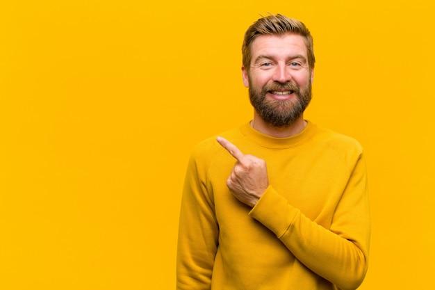Młody blondynka mężczyzna uśmiecha się radośnie, czuje się szczęśliwy i wskazując na bok i do góry, pokazując obiekt w przestrzeni kopii na pomarańczowej ścianie