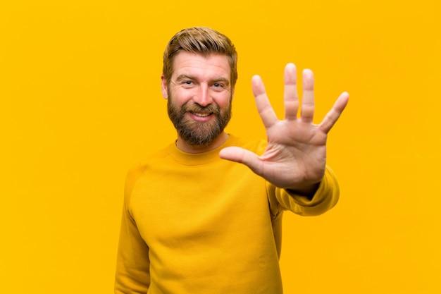 Młody blondynka mężczyzna uśmiechnięty i patrzeje życzliwy, pokazuje liczbę pięć