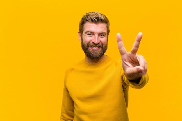 Młody blondynka mężczyzna uśmiechnięty i wyglądający przyjazny, pokazując numer dwa lub drugi ręką do przodu, odliczając do ściany pomarańczowy