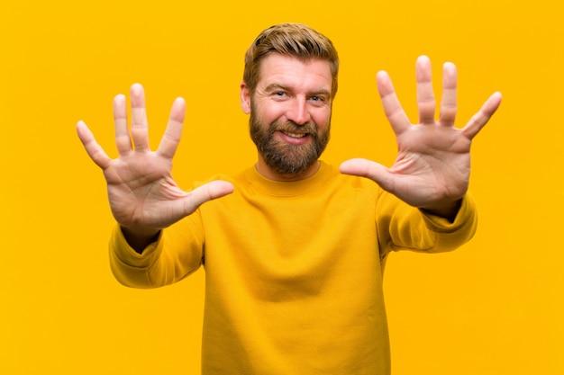 Młody blondynka mężczyzna uśmiechnięty i wyglądający przyjazny, pokazując numer dziesięć lub dziesiąty ręką do przodu, odliczając do ściany pomarańczowy
