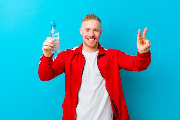 Młody blondynka mężczyzna z butelką wody na sobie ubrania sportowe