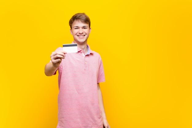 Młody blondynka mężczyzna z kartą kredytową