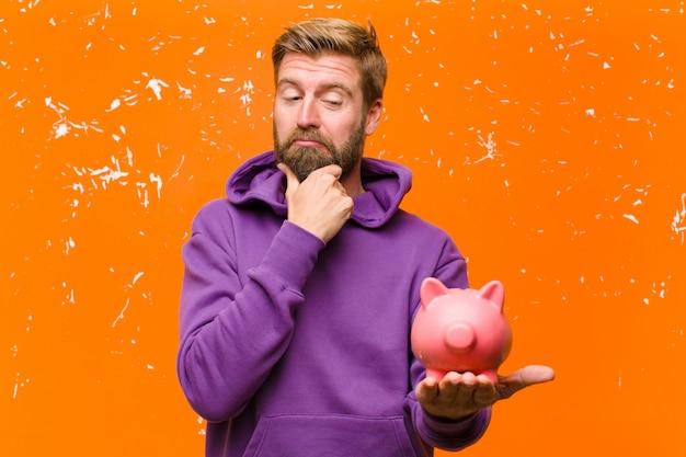 Młody blondynka mężczyzna z skarbonką w fioletowej bluzie z kapturem na uszkodzonej ścianie pomarańczowy
