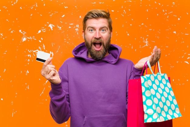 Młody blondynka mężczyzna z torby na zakupy na sobie fioletową bluzę z kapturem przed uszkodzoną ścianę pomarańczowy