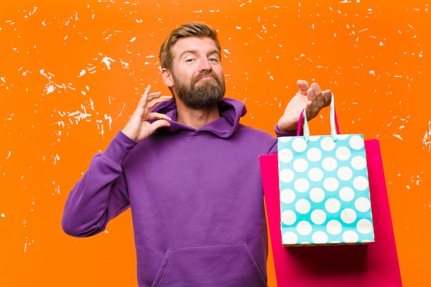 Młody blondynka z torby na zakupy na sobie fioletową bluzę z kapturem na uszkodzonej ścianie pomarańczowy