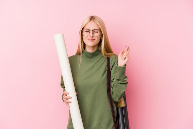 Młody blondynki architektury uczeń krzyżuje palce dla mieć szczęście