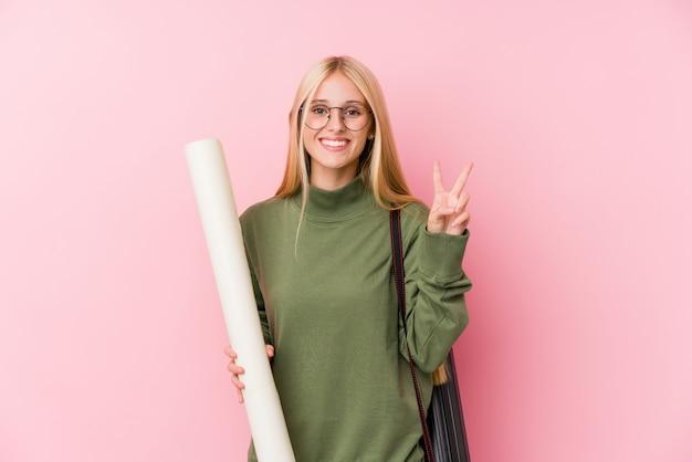 Młody blondynki architektury uczeń pokazuje numer dwa z palcami.