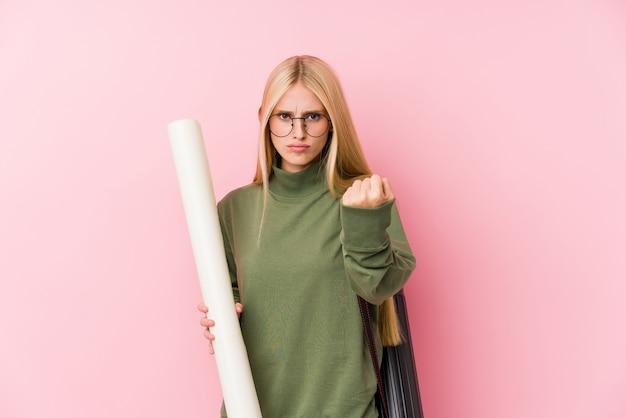 Młody blondynki architektury uczeń pokazuje pięść kamera, agresywny wyraz twarzy.